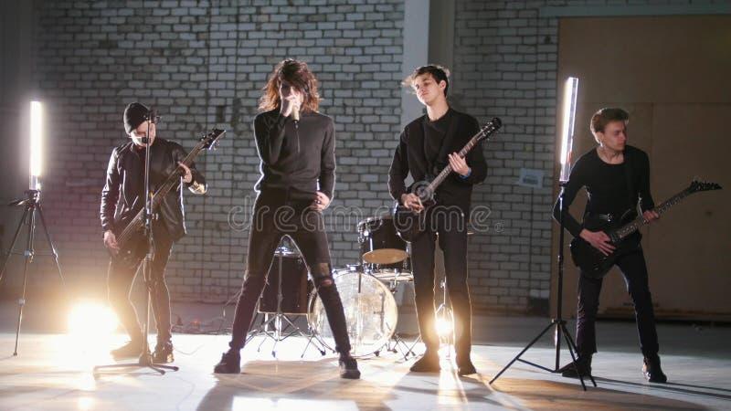 Um grupo rock que tem uma repetição em uma garagem Membros de um grupo que veste a roupa preta imagens de stock royalty free