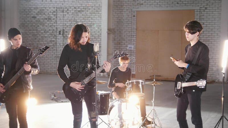 Um grupo rock que tem uma repetição Povos na roupa preta que faz suas partes imagem de stock royalty free