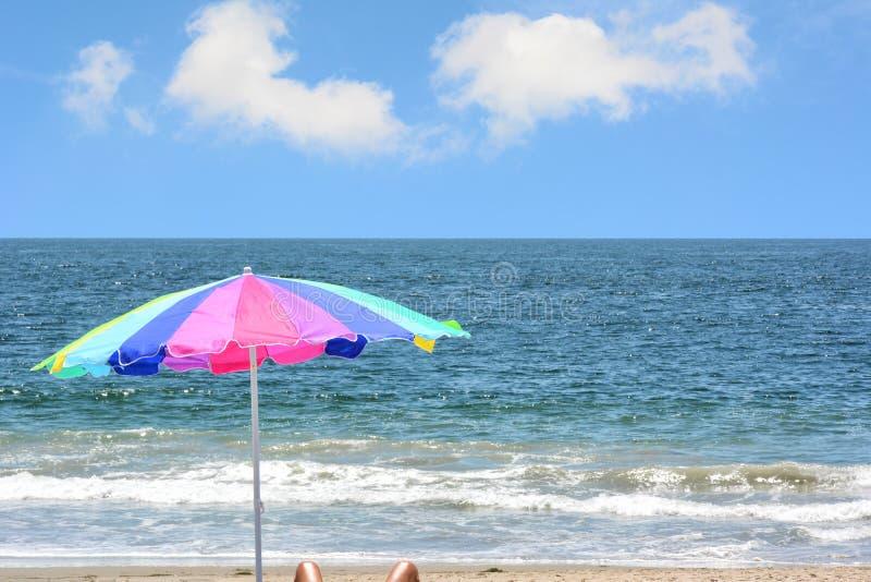 Um guarda-chuva de praia colorido na praia com um céu azul do brigth nuvens macias brancas fotos de stock royalty free