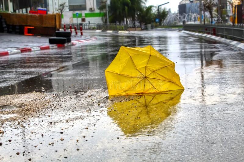 Um guarda-chuva quebrado pelo vento com os pingos de chuva na estrada asfaltada molhada Tempo do inverno em Israel: chuva, poças  fotografia de stock royalty free