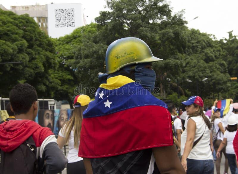 Um guerreiro contra o governo de Nicolas Maduro pronto para protestar a anti máscara de gás lacrimogêneo e bandeira vestindo do v imagens de stock royalty free