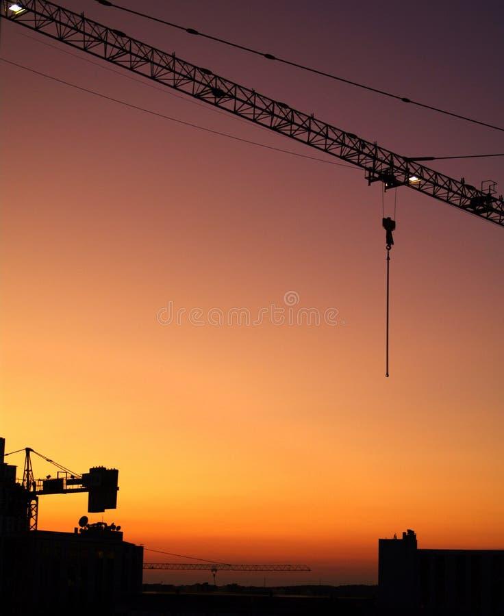 Um guindaste de torre no por do sol fotografia de stock royalty free
