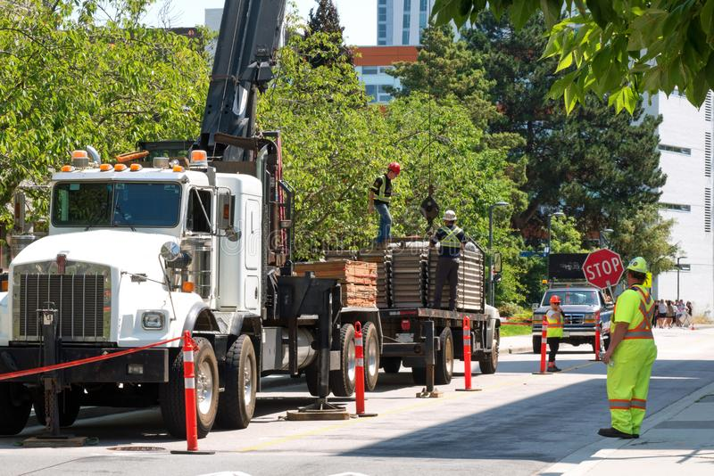 Um guindaste e um caminhão estão na ação em um canteiro de obras da cidade fotografia de stock royalty free