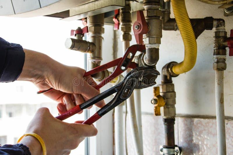 Um gur repara o filtro da caldeira de gás com chaves foto de stock