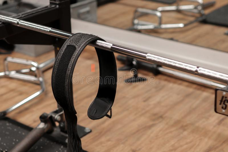 Um gym com uma barra de levantamento do peso e uma correia de levantamento esportes, equipamento de levantamento; imagem de stock
