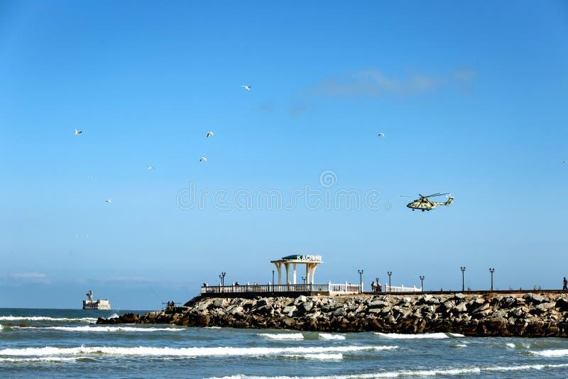 Um helicóptero sobre o mar e um miradouro com uma inscrição no russo Kaspiysk imagens de stock royalty free
