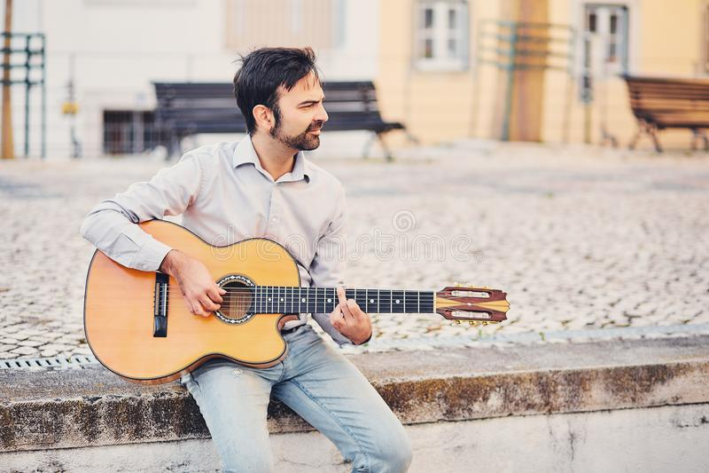 Um homem à moda bonito com uma barba senta-se em um freio concreto na rua e joga-se uma guitarra acústica e sorri-se O músico apr fotografia de stock royalty free