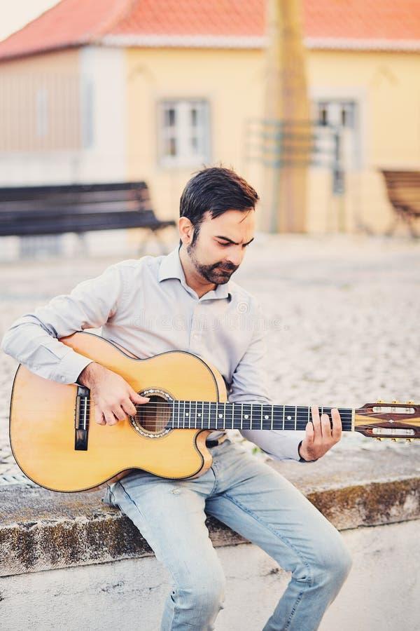 Um homem à moda bonito com uma barba senta-se em um freio concreto na rua e joga-se uma guitarra acústica e sorri-se O músico apr foto de stock