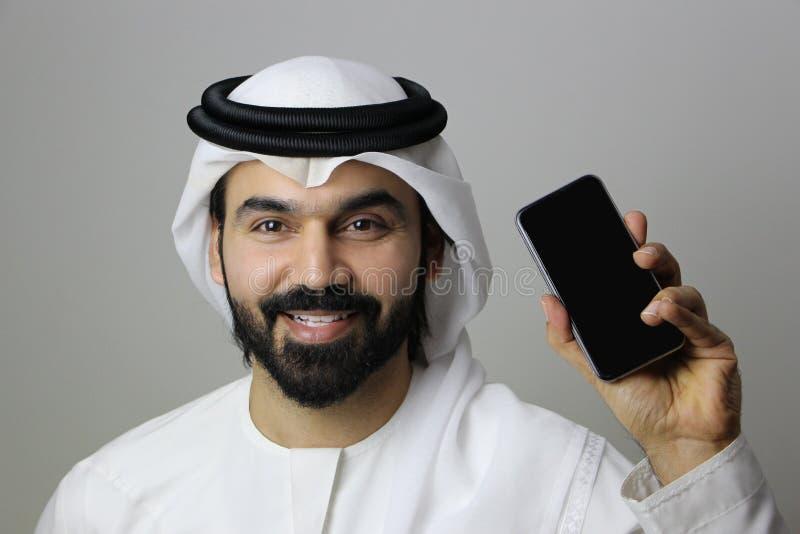 Um homem árabe feliz que guarda um telefone celular imagens de stock