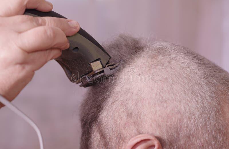 Um homem é cabelo cortado em sua cabeça O penteado do homem no salão de beleza do cabeleireiro fotos de stock