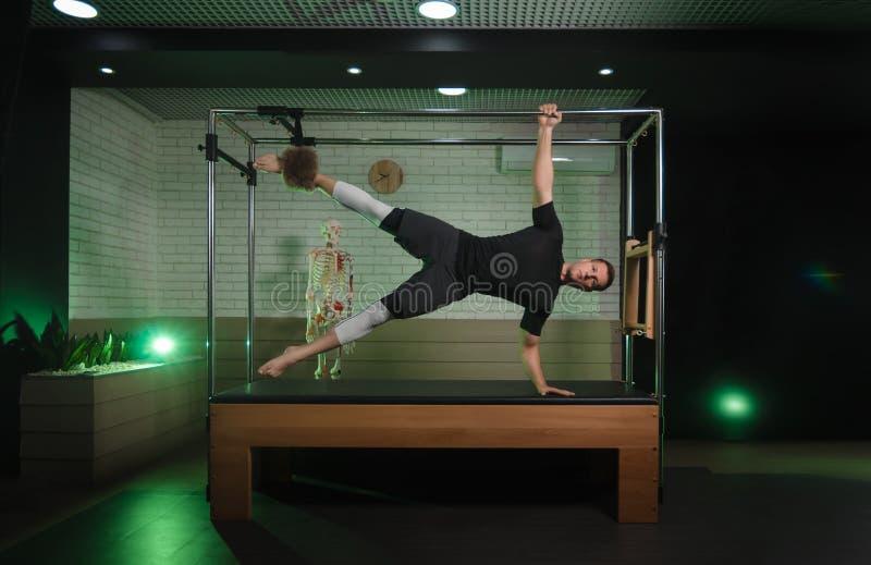 Um homem é contratado em Pilates Aptidão e esportes imagem de stock