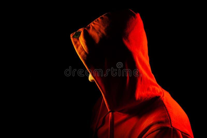 Um homem adulto está o olhar ao lado em uma camiseta encapuçado alaranjada destacada em vermelho e amarelo nos lados sua cara é c imagem de stock royalty free