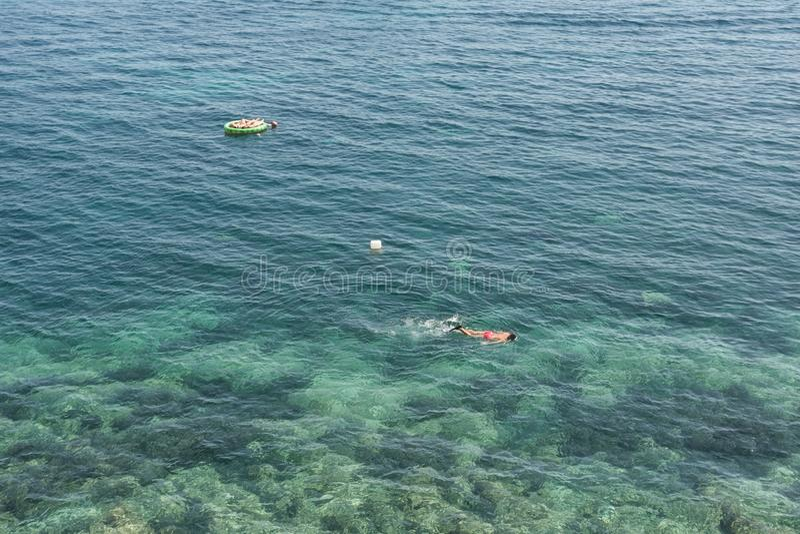 Um homem adulto faz o mergulho autônomo na água clara imagem de stock