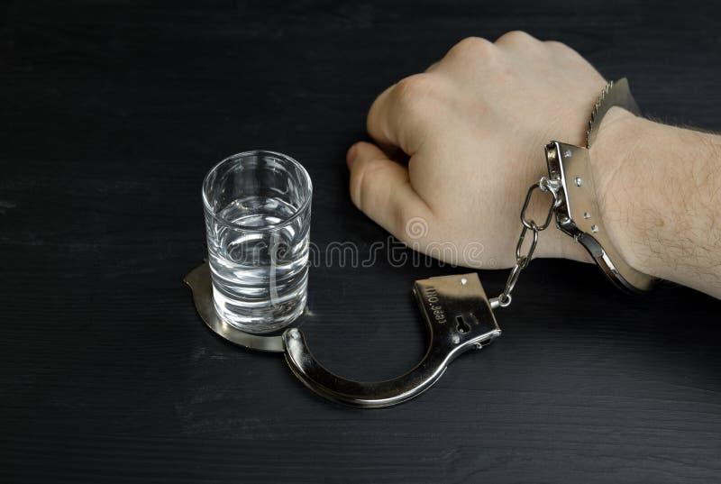 Um homem algemado a um vidro da vodca Apego de álcool ou conceito do alcoolismo foto de stock royalty free