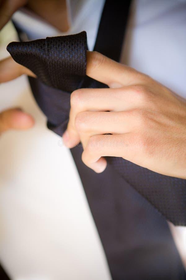Um homem amarra uma gravata fotos de stock