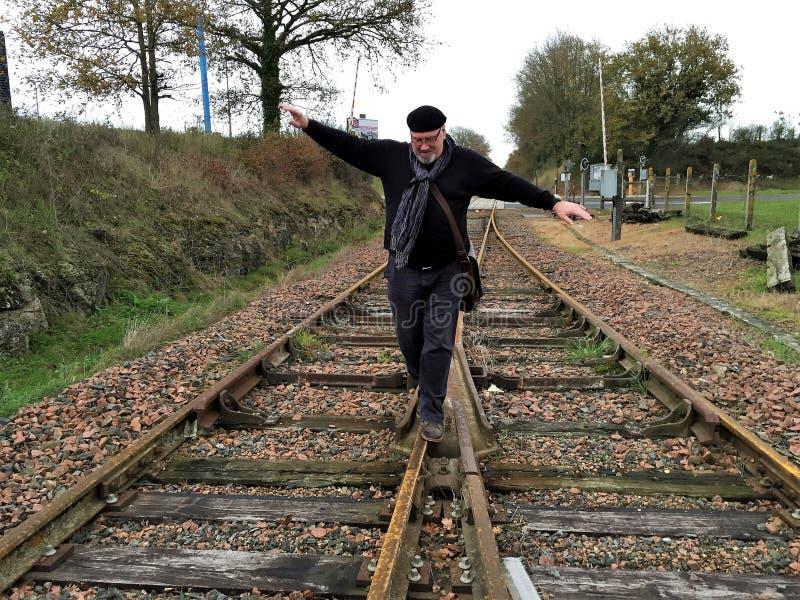 Um homem anda ao longo das trilhas de estrada de ferro fotografia de stock royalty free