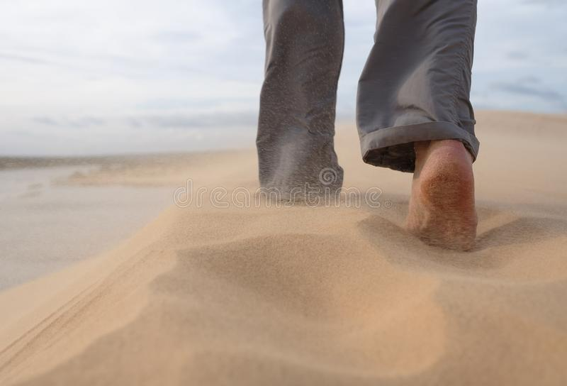 Um homem anda ao longo do Sandy Beach No ar, grões da mosca de areia de um forte vento foto de stock