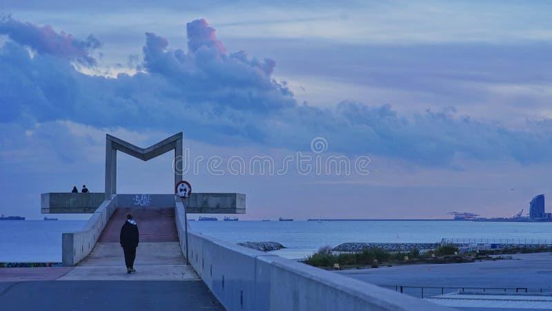 um homem anda para a plataforma do mar imagens de stock royalty free