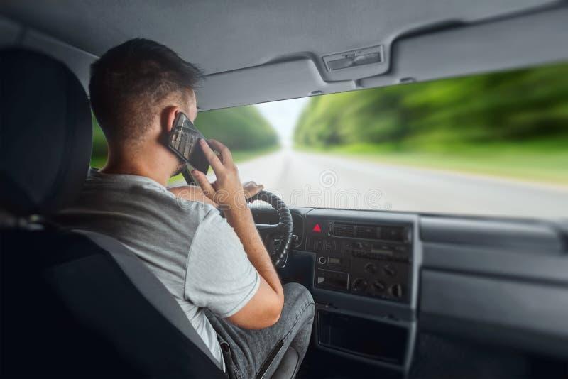 Um homem ao volante segurando um smartphone em sua mão, viola regras de trânsito O conceito de acidente, de violação de trânsito, imagem de stock royalty free