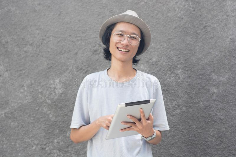 Um homem asiático criativo atractive novo com chapéu e vidros do fedora usando a tabuleta e sorrindo na câmera fotografia de stock