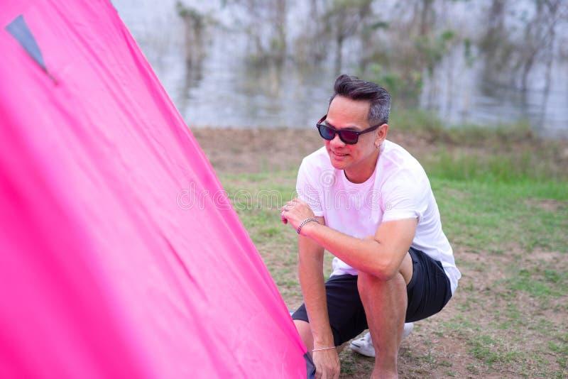 Um homem asiático na camisa branca de t que ajusta a barraca cor-de-rosa fotografia de stock