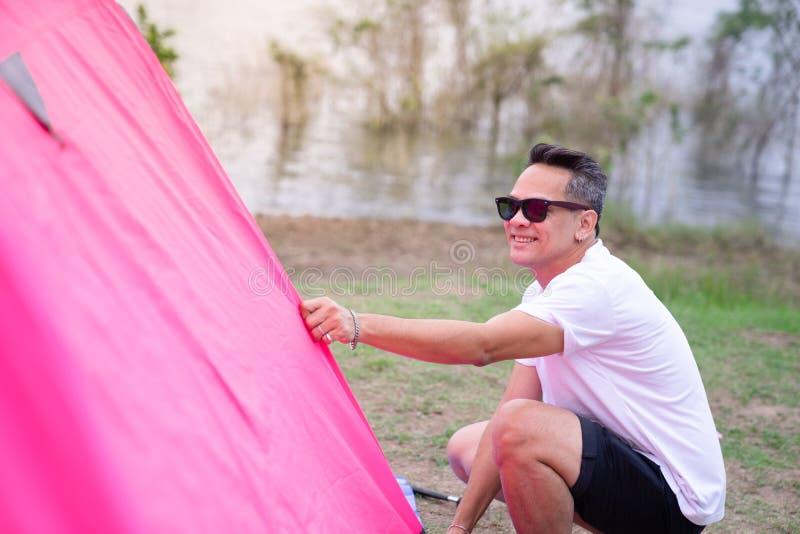 Um homem asiático na camisa branca de t que ajusta a barraca cor-de-rosa fotografia de stock royalty free