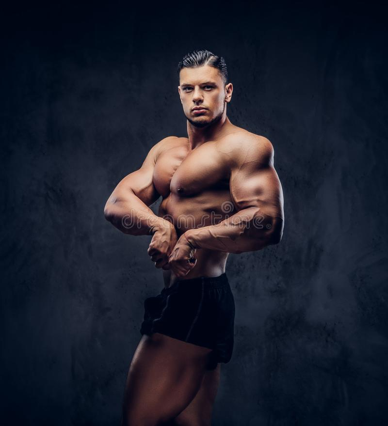 Um homem atlético considerável com posição do corpo muscular na pose competitiva do halterofilista imagens de stock royalty free