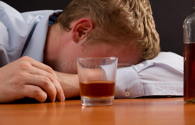 Um homem bêbado está adormecido na tabela fotografia de stock