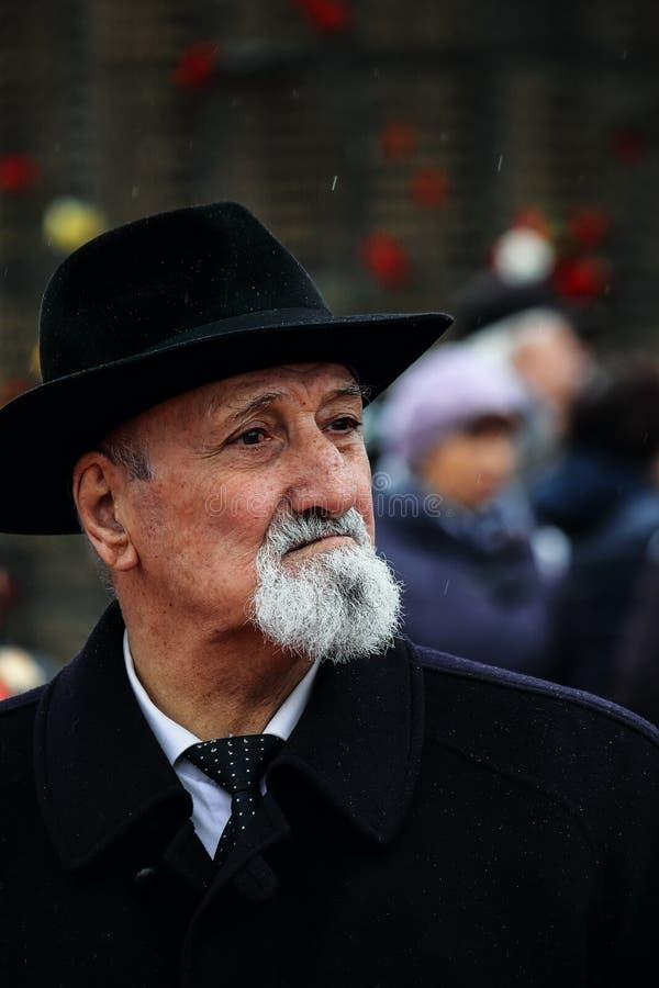 Um homem branco com uma barba cinzenta em um chapéu negro e em um revestimento está olhando pensativamente ao lado imagem de stock royalty free
