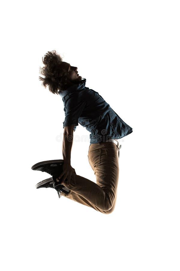 Um homem breakdancing do dançarino acrobático novo caucasiano da ruptura no fundo do branco da silhueta fotografia de stock