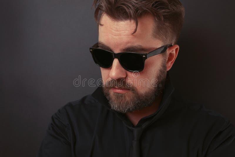 Um homem brutal com uma barba e um penteado à moda em um terno preto e em óculos de sol imagem de stock royalty free