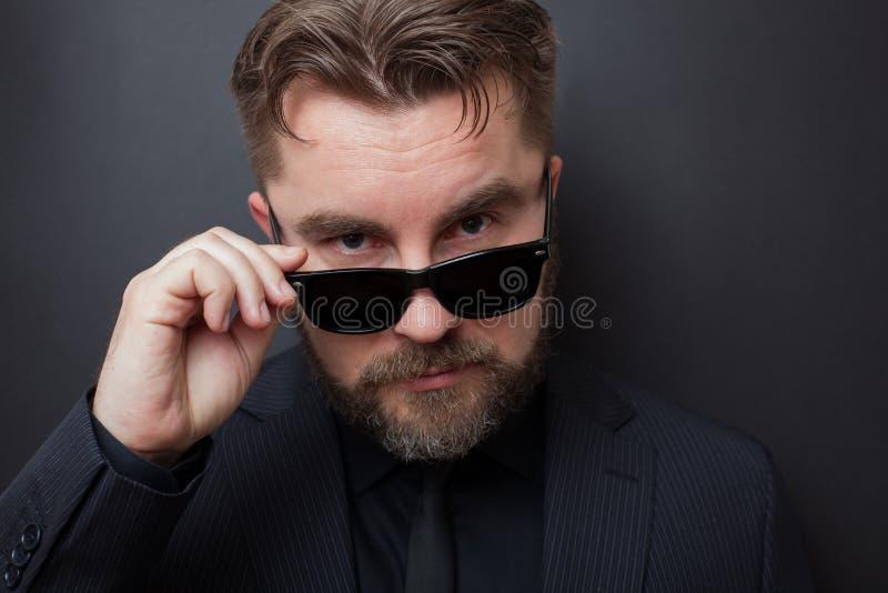 Um homem brutal com uma barba e um penteado à moda em um terno preto olha appallingly na câmera, deixando cair seus óculos de sol foto de stock