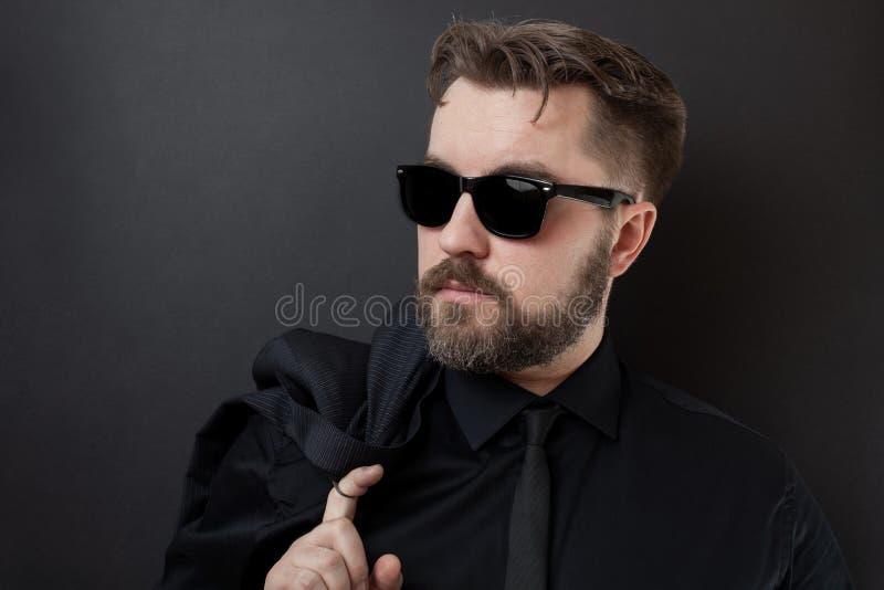 Um homem brutal com uma barba e um penteado à moda em uma camisa e em um laço pretos está guardando seu revestimento Homem de neg imagem de stock