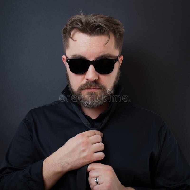 Um homem brutal com uma barba e um penteado à moda em uma camisa preta ajusta seu laço O homem de negócios nos óculos de sol amar imagens de stock royalty free
