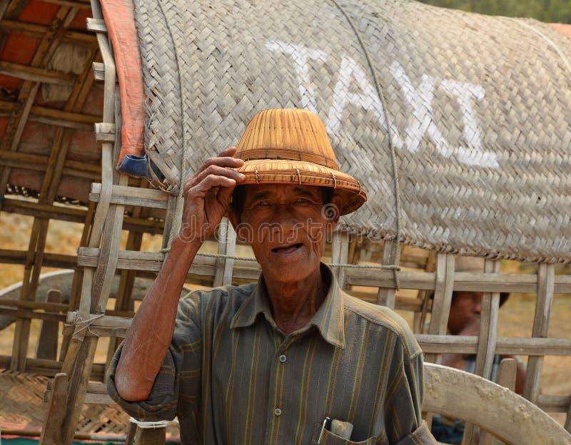 Um homem burmese idoso não identificado do táxi na frente do transporte imagem de stock