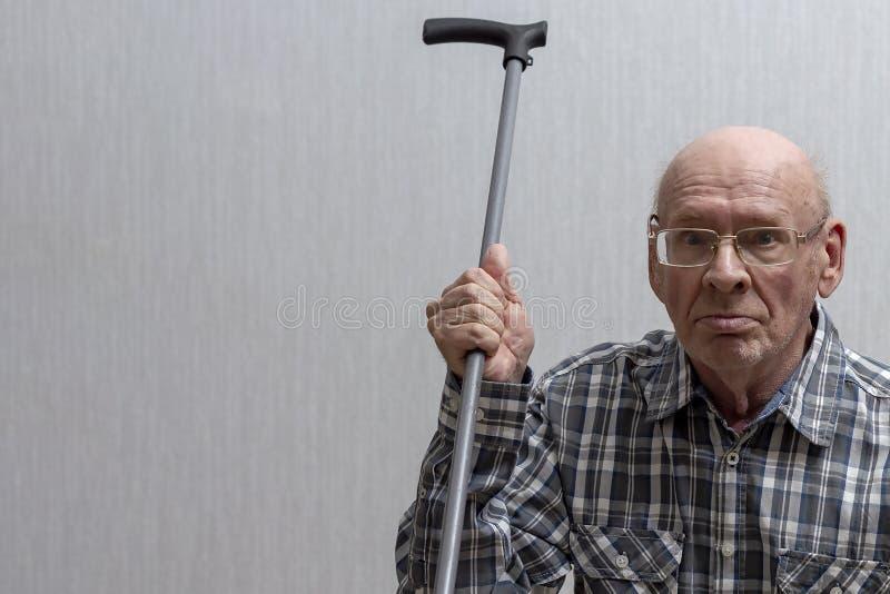 Um homem calvo idoso com vidros est? acenando uma vara de passeio fotografia de stock