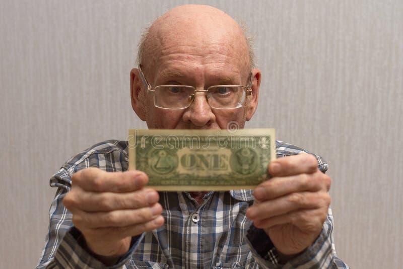 Um homem calvo idoso com vidros guarda uma c?dula na frente dele - um d?lar americano fotografia de stock