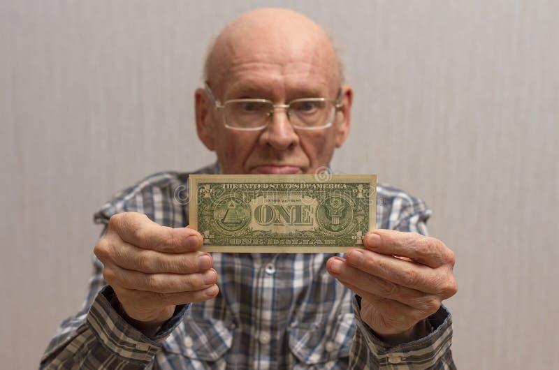 Um homem calvo idoso com vidros guarda uma c?dula na frente dele - um d?lar americano foto de stock
