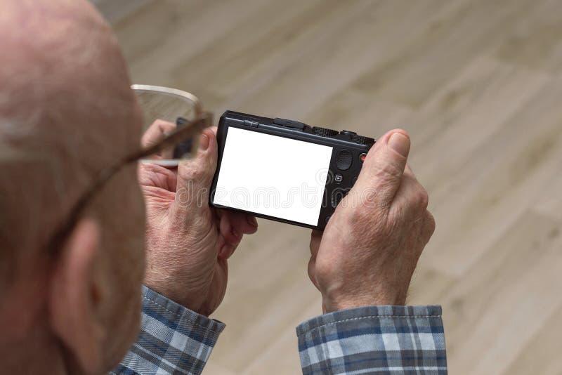 Um homem calvo idoso com vidros olha a metragem na c?mera Copie o espa?o foto de stock royalty free