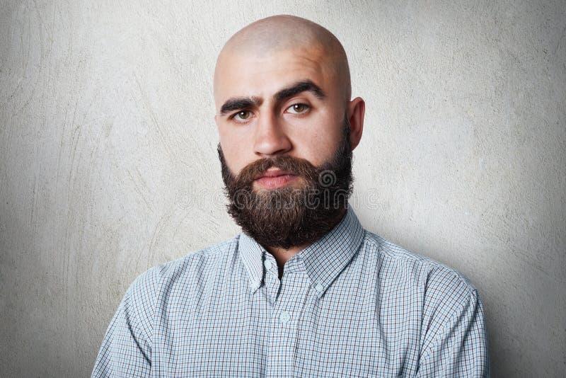 Um homem calvo seguro com as sobrancelhas pretas grossas e barba que veste a camisa verificada que tem a expressão sombrio que le fotos de stock royalty free