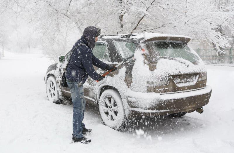 Um homem cancela a neve de seu carro durante uma queda de neve imagens de stock