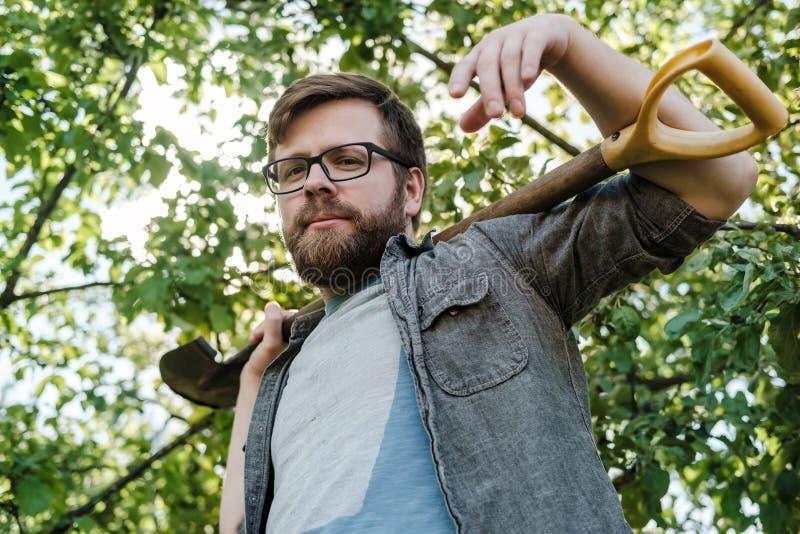Um homem caucasiano novo com uma barba e nos vidros mantém uma pá em seus ombros e olhares na câmera, contra foto de stock
