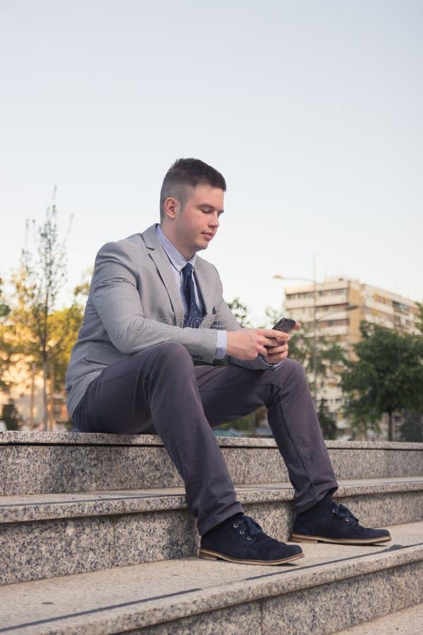 Um homem caucasiano novo que sorri, terno de negócio, vestuário formal, ord fotos de stock