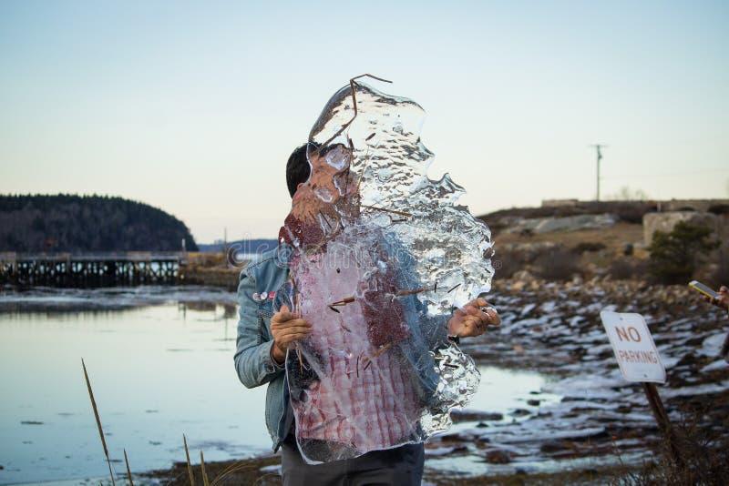 Um homem caucasiano que guarda uma parte giganctic de gelo em suas mãos com um lago no fundo foto de stock royalty free