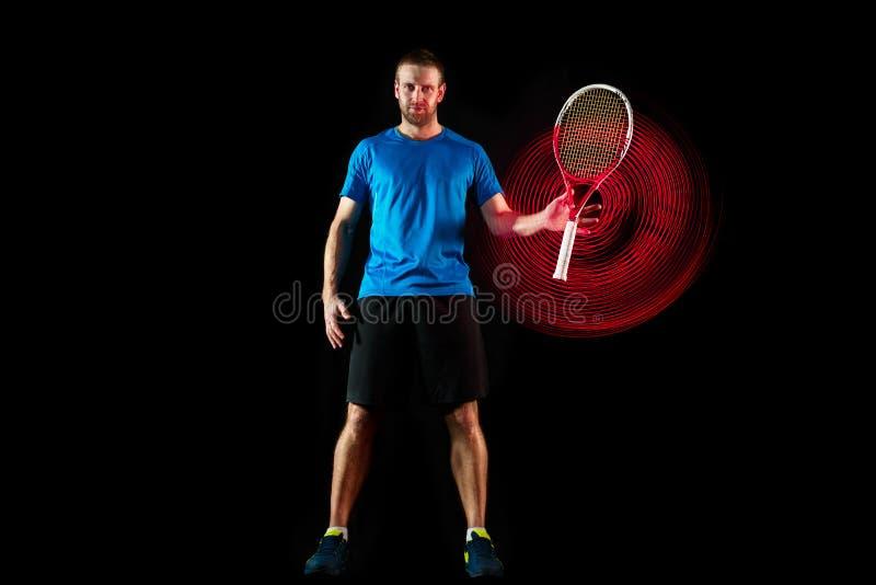 Um homem caucasiano que joga o jogador de tênis no fundo preto imagem de stock royalty free