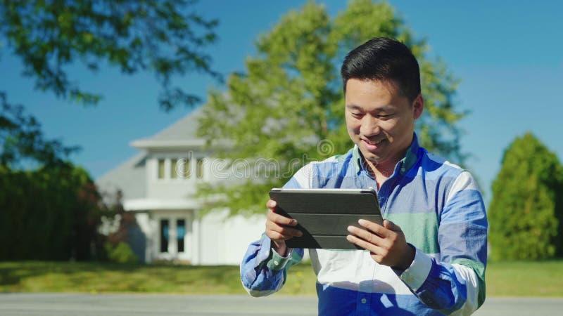 Um homem chinês alegre usa uma tabuleta perto de sua casa fotos de stock