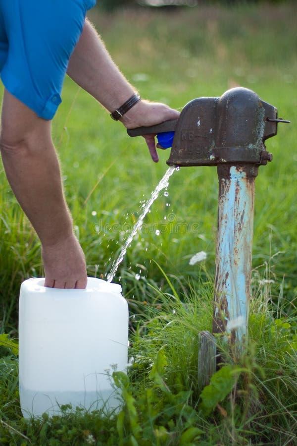Um homem coleta a água de fotografia de stock royalty free