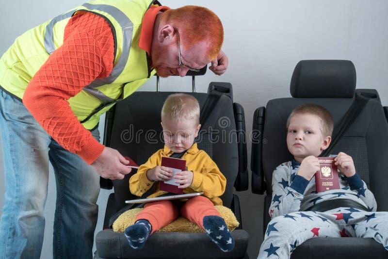 Um homem com cabelo vermelho verifica seu passaporte Uma criança pequena feliz está sentando-se no cinto de segurança do carro O  imagem de stock