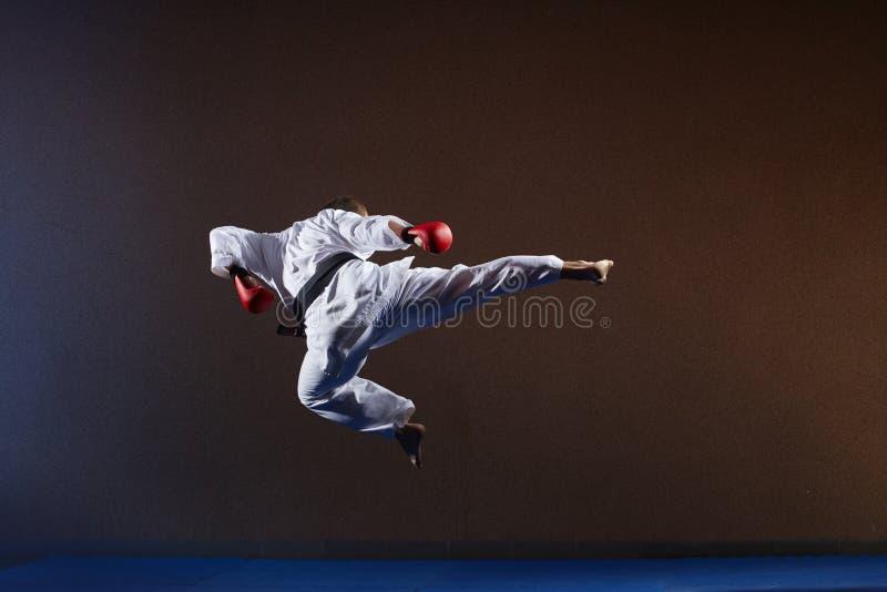 Um homem com um cinturão negro bate um pontapé em um salto foto de stock royalty free