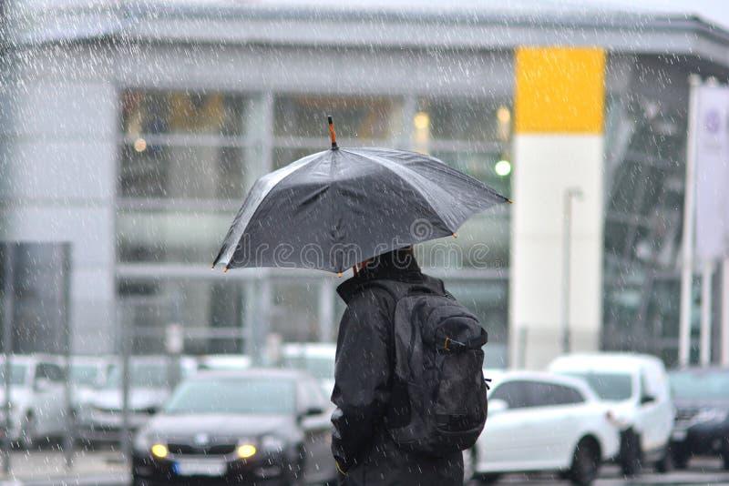 Um homem com um guarda-chuva na chuva que cruza a estrada imagem de stock